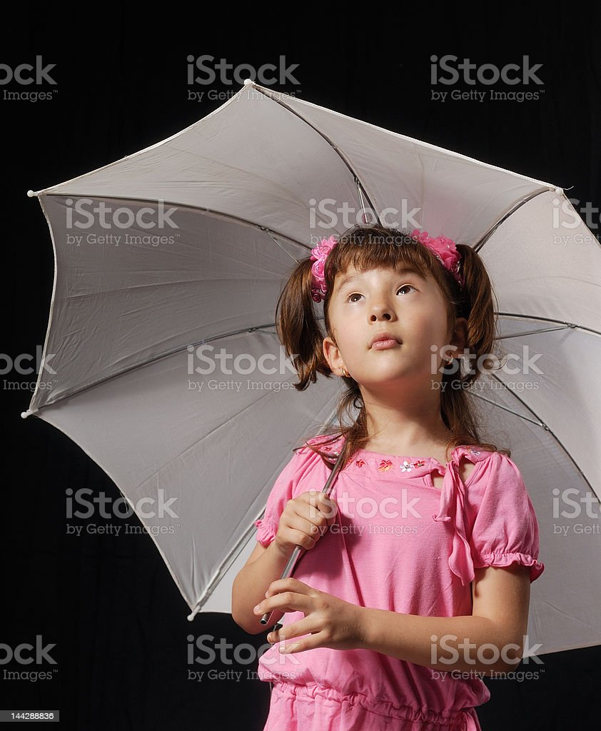Little Asian girl in pink dress under umbrella looking up royalty-free stock photo
