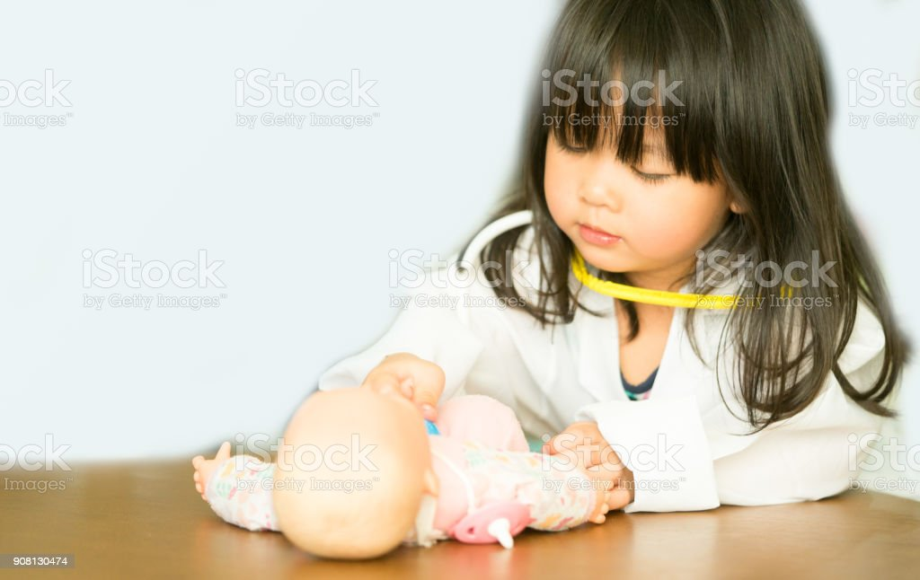 Little asian girl play with baby doll toy.Little asian girl hold stethoscope in hand and check baby doll toy. stock photo
