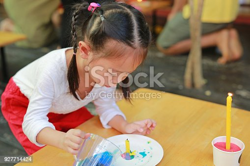 istock Little Asian girl pouring solution into a plate. Science experiments for young scientist learning. 927714424