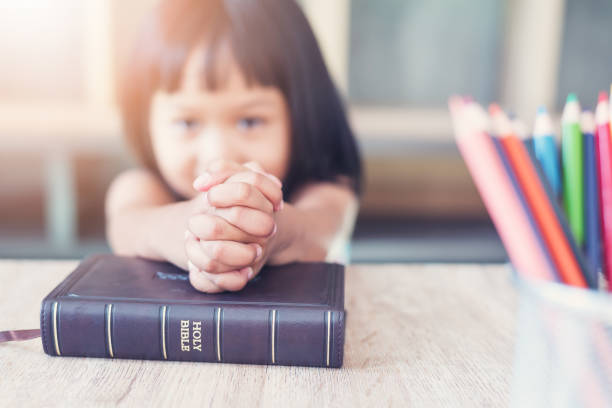 Little Asian girl pray with bible in classroom at school, bible study concept Little Asian girl pray with bible in classroom at school, bible study concept catholicism stock pictures, royalty-free photos & images