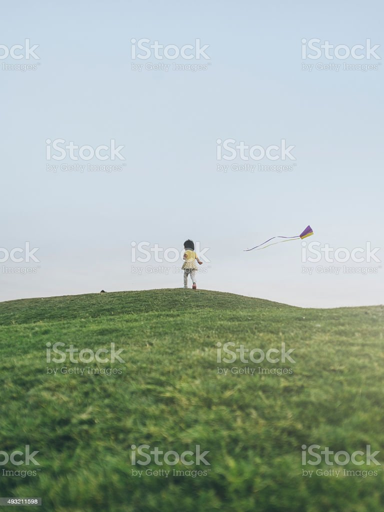 little asian girl running to kite on lawn stock photo