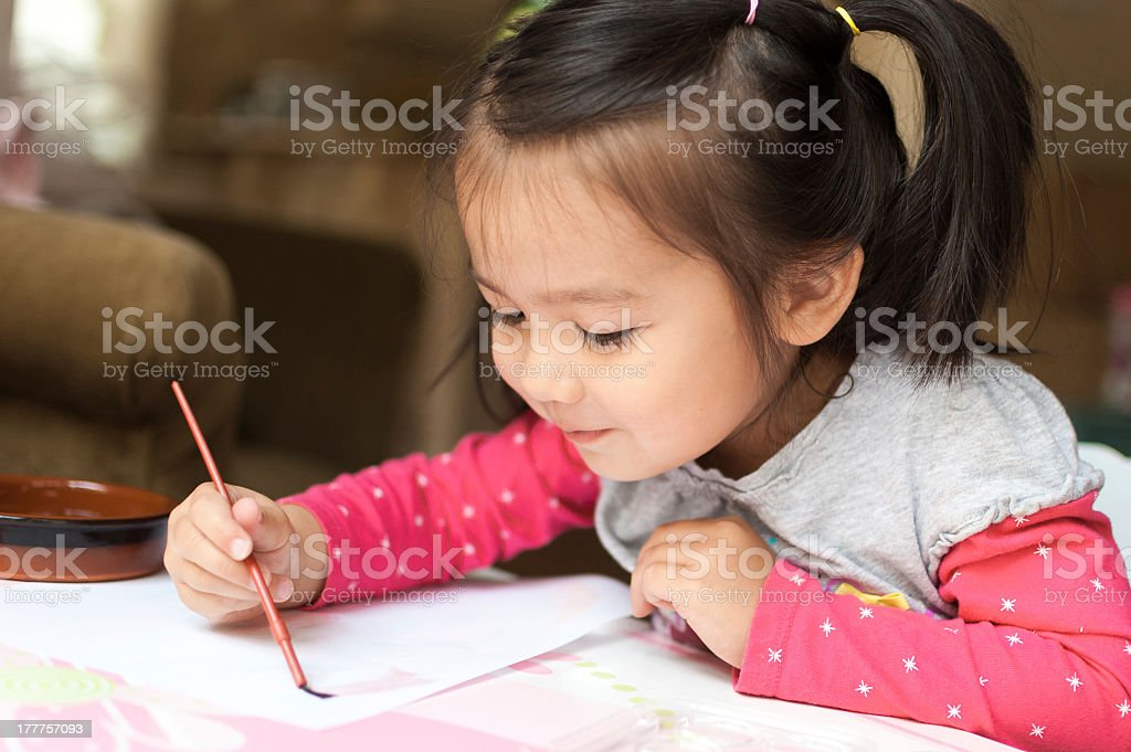 Little Asian girl sitting down learning to paint stock photo