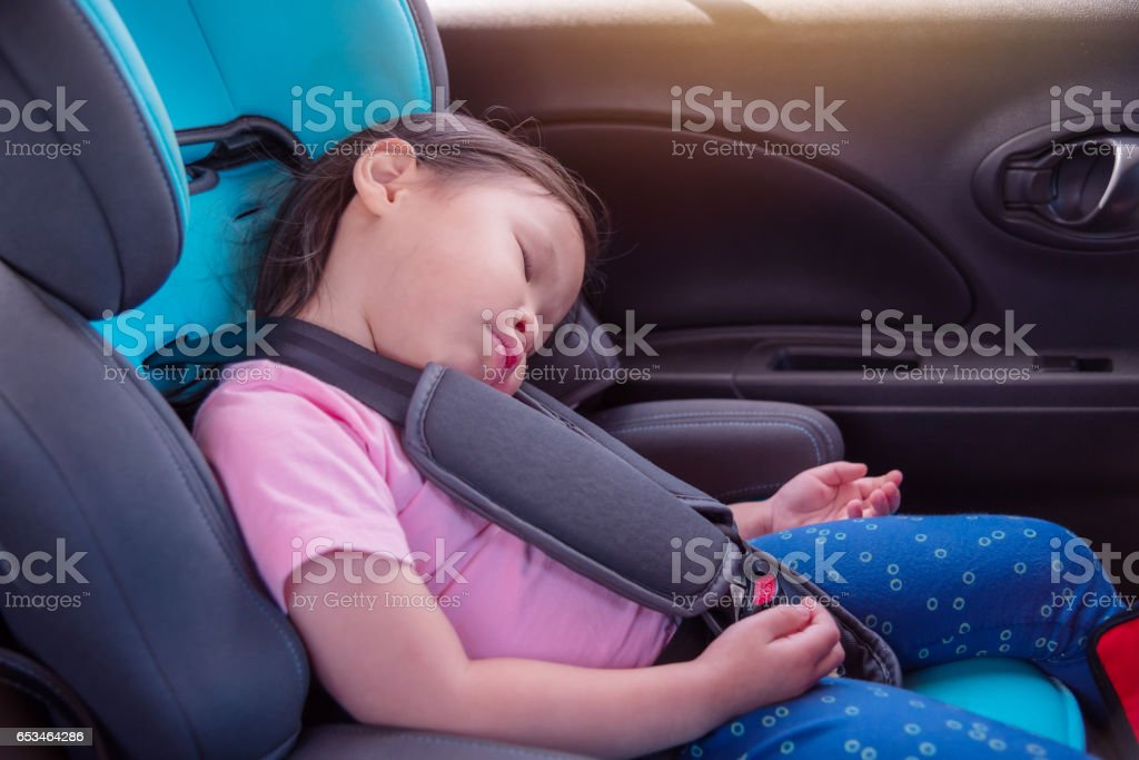 Little asian girl sleeping on car seat in car stock photo