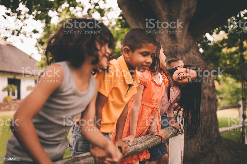 Little asian girl smiling on fence with friends in park stock photo