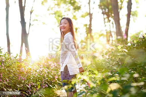 8 year-old beautiful little asian girl standing in flower field looking back and smiling.