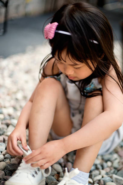 Little asian girl trying to tie her shoes outdoors. stock photo