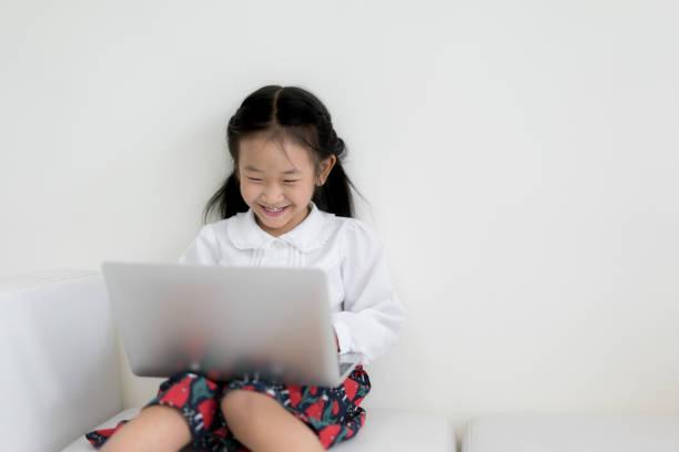 Kleine Asiatin mit Laptop zu studieren. Bildung, Freizeit, Technik und Internet-Konzept. – Foto