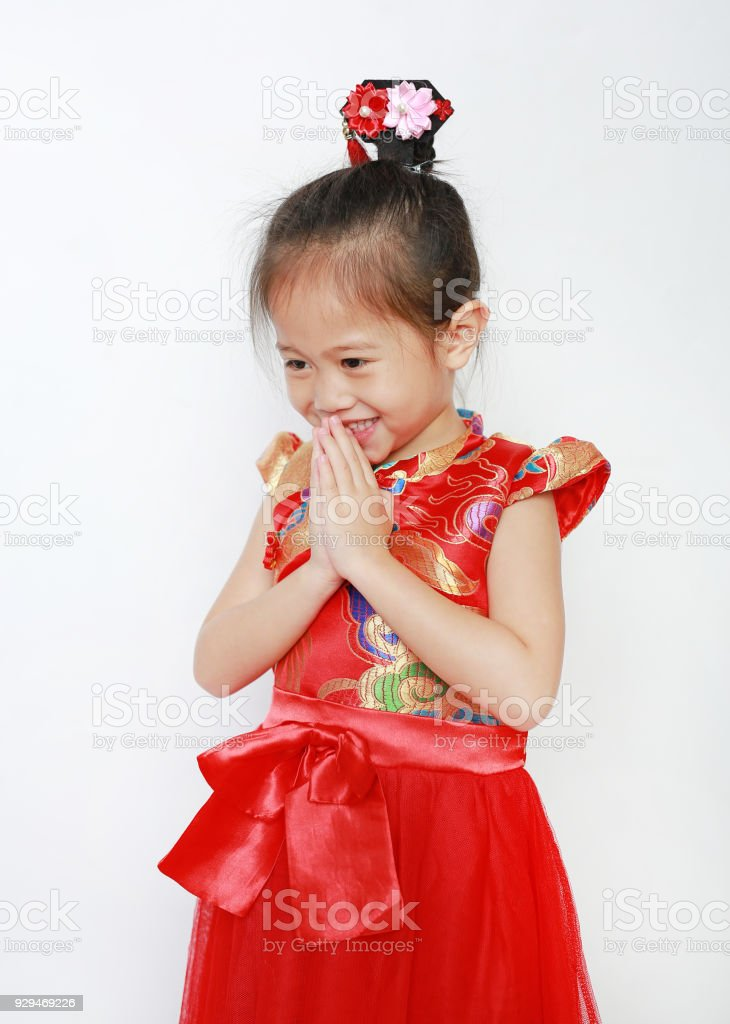Little Asian girl wearing red cheongsam with Respect 'Sawasdee' isolated on white background. Happy Chinese new year. stock photo