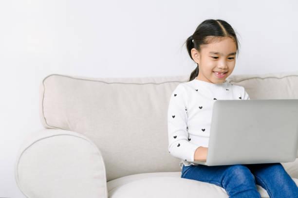 Kleine asiatische Mädchen mit Laptop-Computer oder Notebook in lebenden rom zu Hause. Lernkonzept. Online-Shopping-Konzept. – Foto