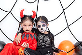 istock Little asian girls sitting and smile in room decorated for Halloween day 1167572101