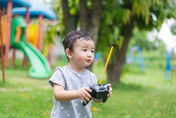 Little Asian kid holding a radio remote control. shallow DOF stok fotoğrafı