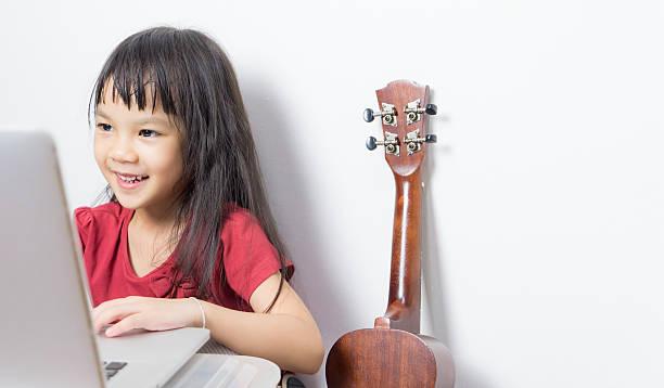 Little Asian musician is taking music class online. - foto de stock
