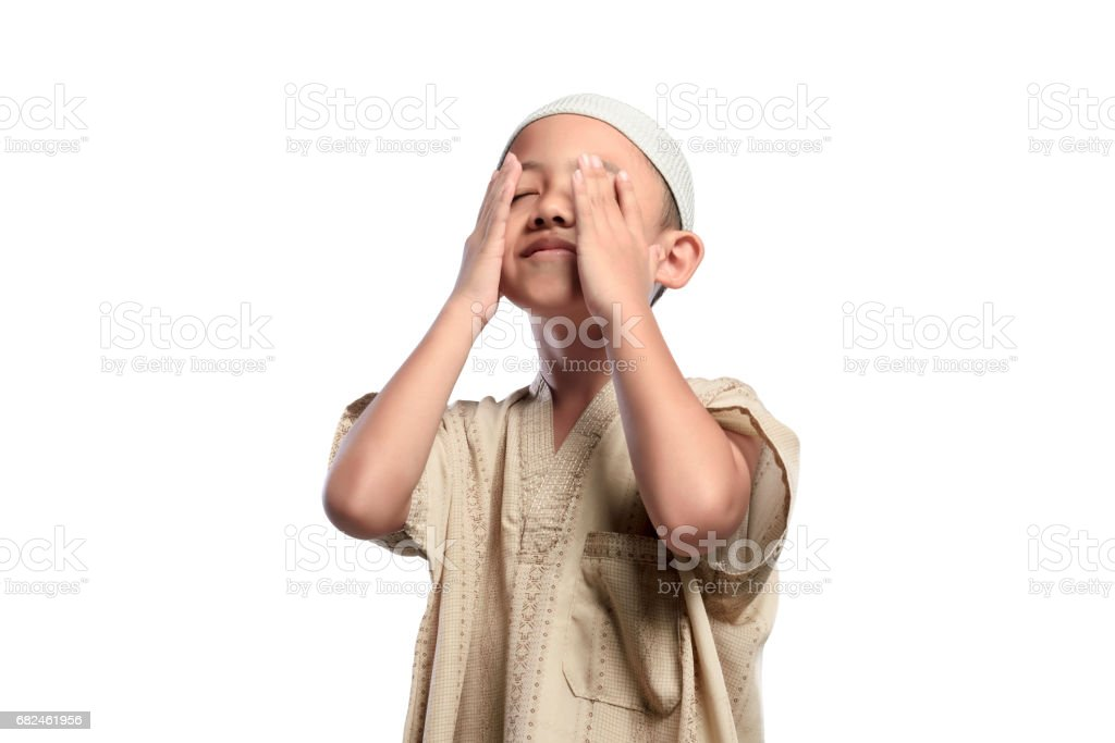 Little asian muslim kid with white cap praying royalty-free stock photo