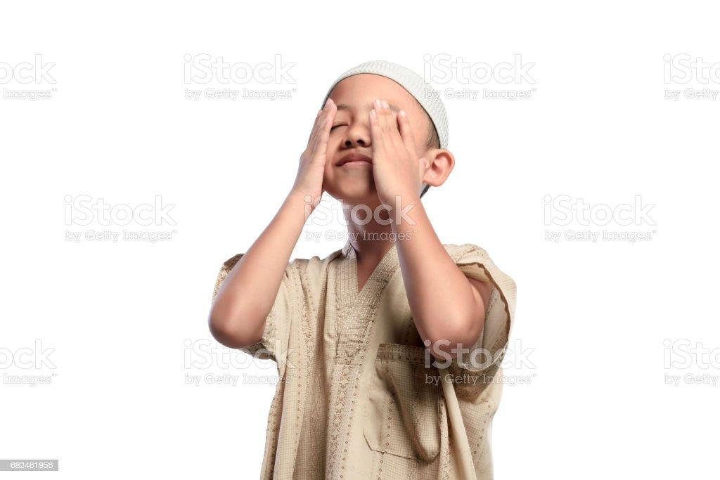 Little asian muslim kid with white cap praying photo libre de droits