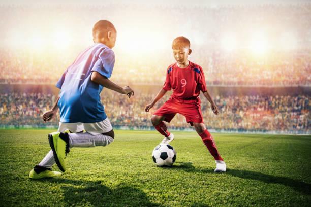 pequeños niños de fútbol asiáticos en acción en el estadio - foto de stock