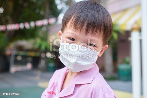 Cute little Asian 3 - 4 years old toddler boy child wearing protective medical mask at school, Concept of coronavirus quarantines and Air pollution pm2.5 concept