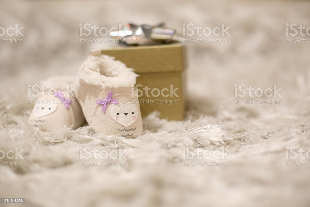 Little baby booties and gift boxes stock photo