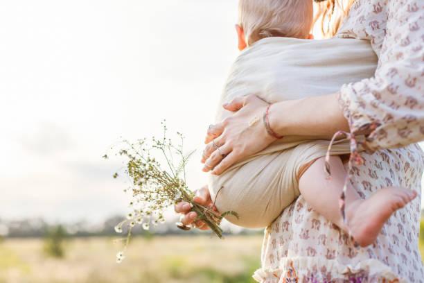Kleinen Jungen und seiner Mutter zu Fuß in den Bereichen Sommertag. Mutter hält und ihr Baby im Tragetuch Babytrage kitzeln. Konzept der natürlichen Erziehung – Foto