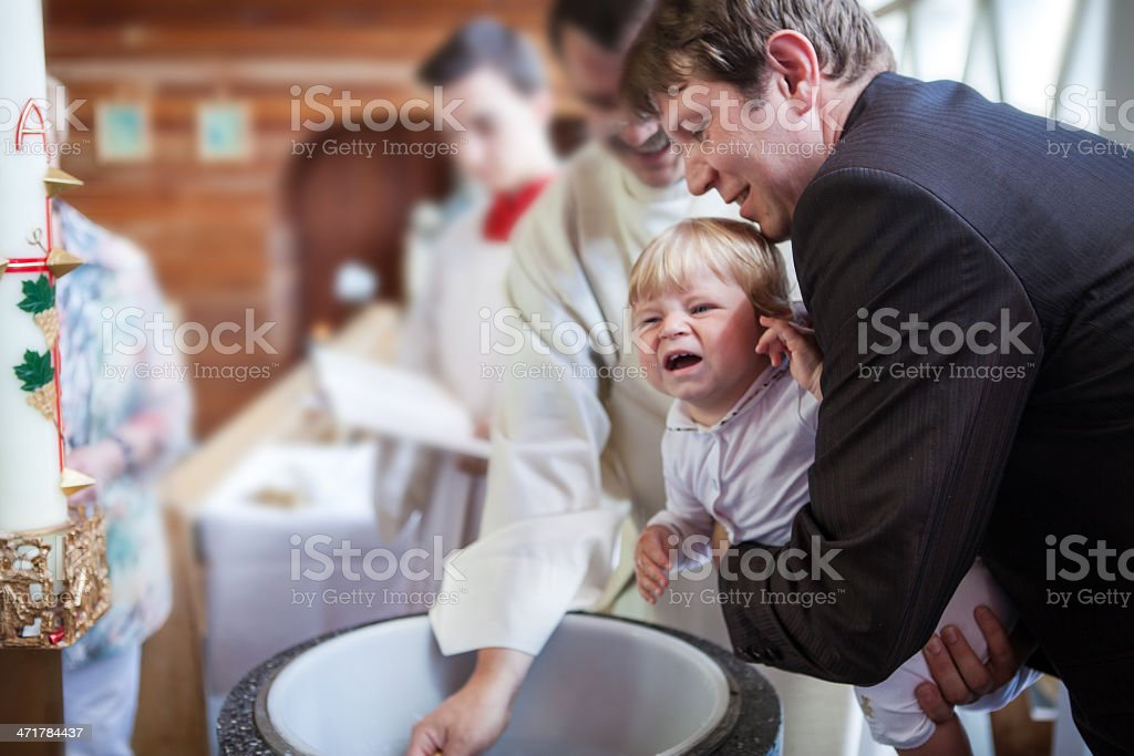 Little baby boy being baptized stock photo