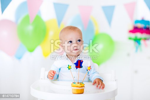 istock Little baby boy celebrating first birthday with colorful cup cake 614710794