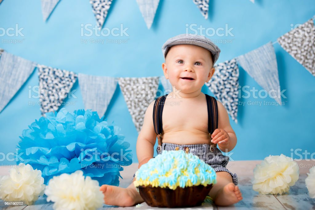 Little baby boy, celebrating his first birthday with smash cake party, studio isolated shot on blue stock photo