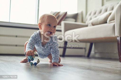 little baby boy crawling on floor at home.