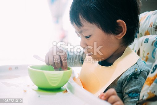 istock Little baby boy eating food on high chair. 1032721310
