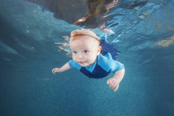 Little baby boy in a blue wetsuit learns to swims underwater in the swimming pool. Healthy family lifestyle and children water sports activity. Child development, disease prevention stock photo