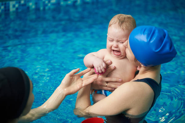 Little baby boy in diaper crying, afraid of water and swimming. Mother calming baby, holding on hand and kissing baby Little blond baby boy in diaper crying, afraid of water and swimming. Mother calming baby, holding on hand and kissing her baby. Women accustoming small child to water and teaching swimming in pool kissinghand stock pictures, royalty-free photos & images
