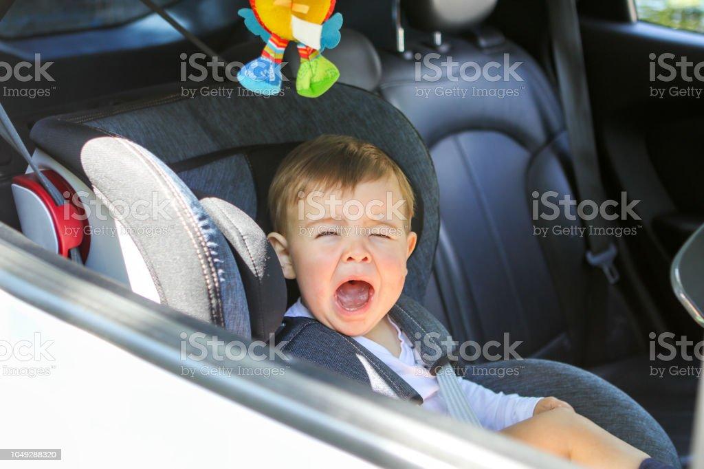 Niño bebé llora en su asiento de coche no dispuesto a sentarse en él. Viajando con concepto de seguridad de niño y bebé. Poco transporte de pasajeros - Foto de stock de 12-17 meses libre de derechos