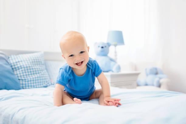 küçük oğlu beyaz yatakta - baby teeth stok fotoğraflar ve resimler