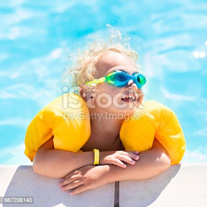 istock Little baby boy playing in swimming pool 667206140