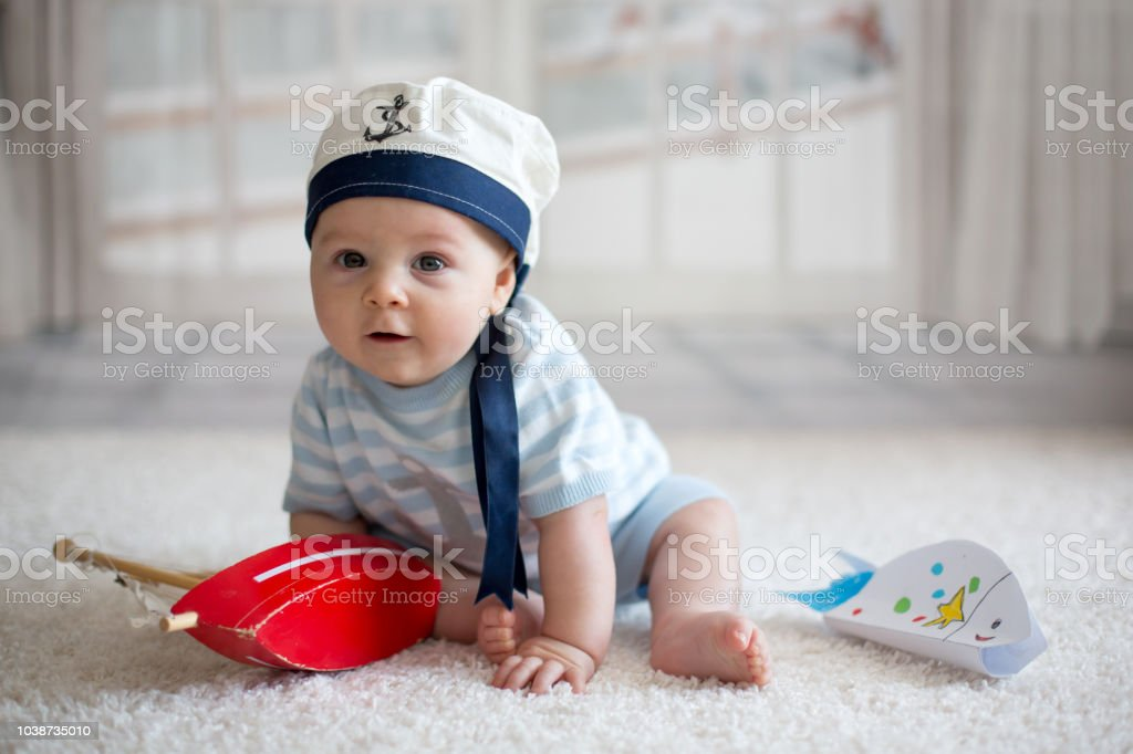 Little baby boy, playing wtih little boat and little fish at home,...