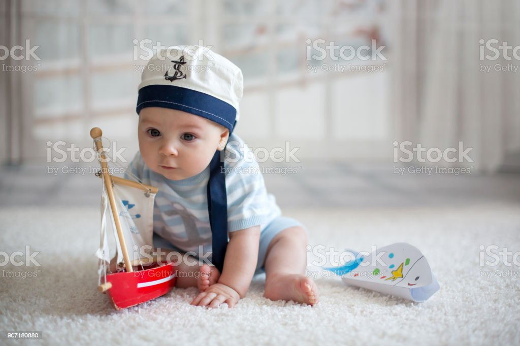 Little baby boy, playing wtih little boat and little fish at home stock photo