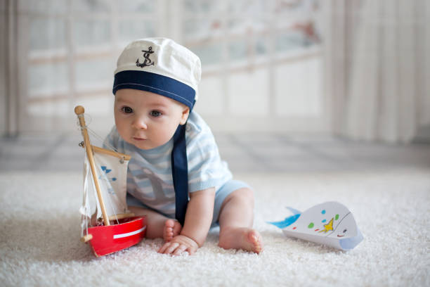 Little baby boy, playing wtih little boat and little fish at home Little baby boy, playing wtih little boat and little fish at home, having sailor hat sailor stock pictures, royalty-free photos & images