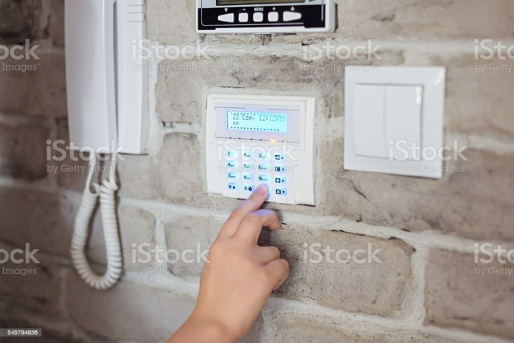 Little baby boy pushes a buttons on the alarm keypad – Foto