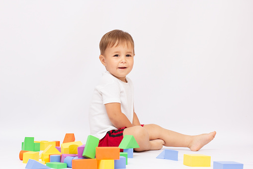 A little baby boy sitting on the floor playing with cubes smiling, isolated on a white background.