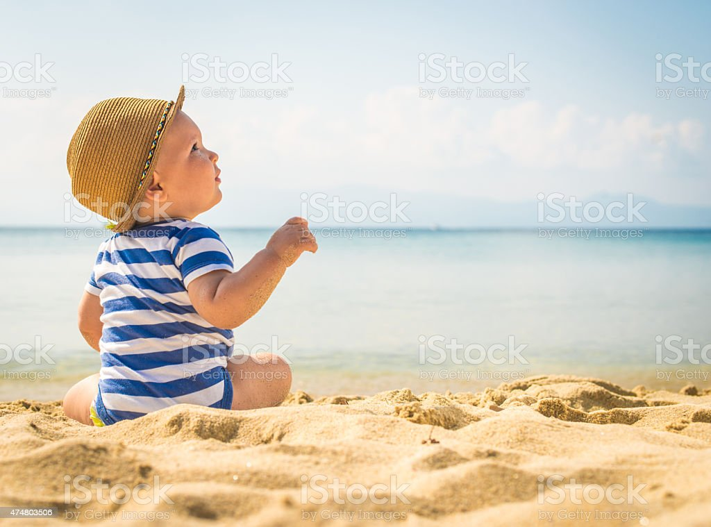 Little baby boy sentada en la arena de la playa - foto de stock