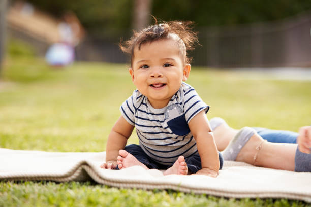 Little baby boy sitting up on a blanket in the park looking to camera, close up stock photo