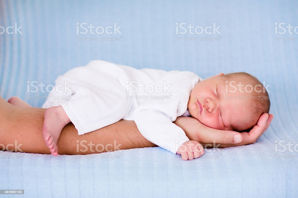 Little baby boy sleeping in arms of his father Newborn baby sleeping in arms of his father. Dad holding new born son. Child taking a nap on parent hand. Infant kid sleeping on a blue blanket. Textile bedding for kids. Parents and children bonding. 2015 Stock Photo