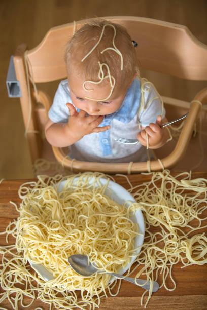 Pequeño niño, niño pequeño, comer espaguetis para el almuerzo y hacer un desastre - foto de stock