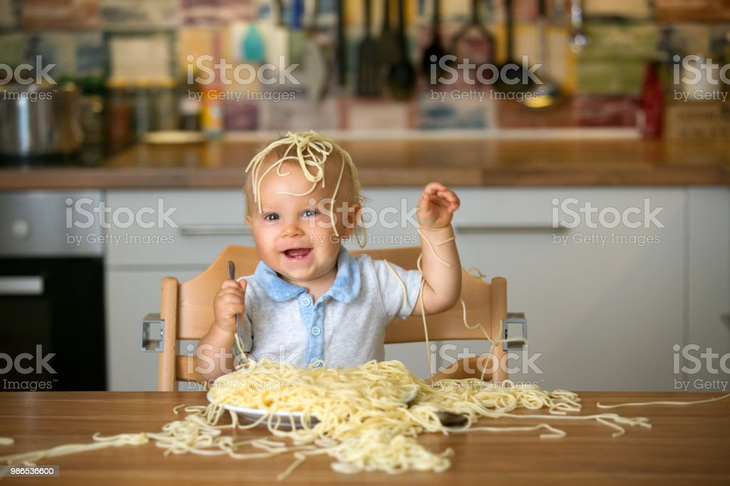 Little baby boy, toddler child, eating spaghetti for lunch and making a mess - fotografia de stock