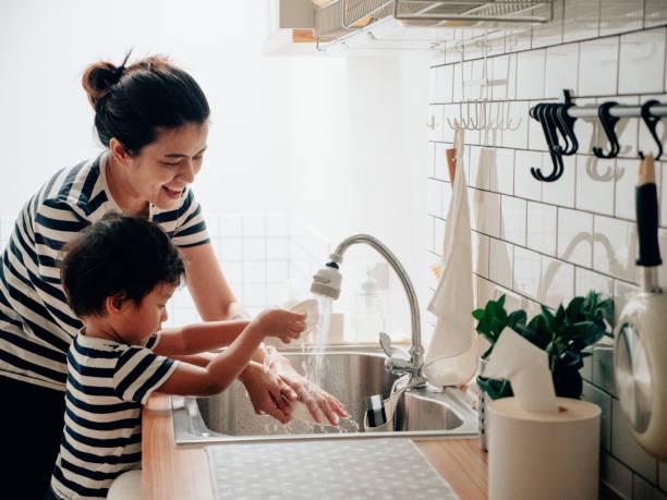 小さな男の子は彼の母親と一緒にきれいな料理を拭きます。 - 東洋民族 ストックフォトと画像