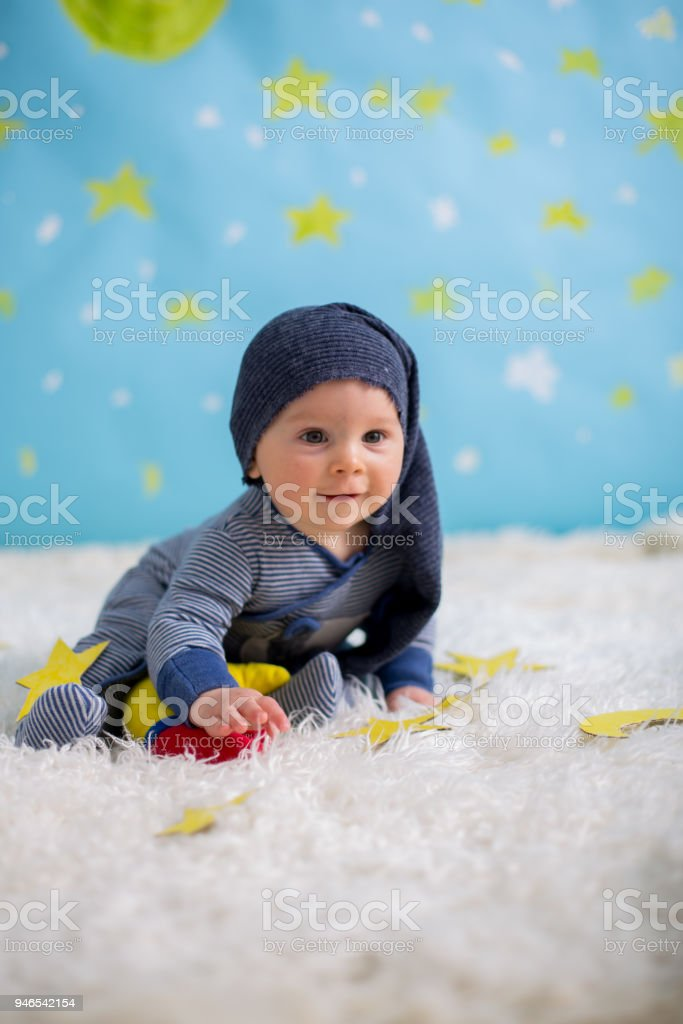 Little baby boy with cute teddy bear and moon on a blue star and moon background stock photo