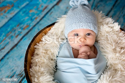 Little baby boy with knitted hat in a basket, happily smiling and looking at camera, isolated studio shot