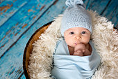 Little baby boy with knitted hat in a basket, happily smiling