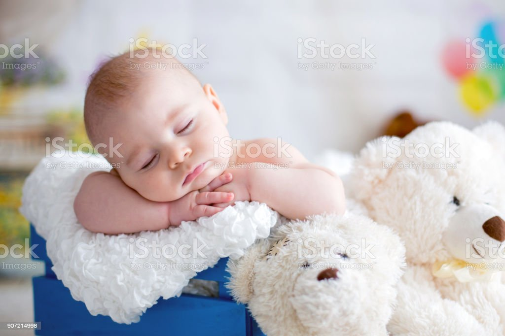 Little baby boy with knitted hat, sleeping with cute teddy bear stock photo