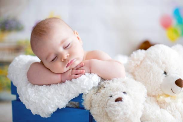 Bebé niño con sombrero hecho punto, dormir con lindo oso de peluche - foto de stock