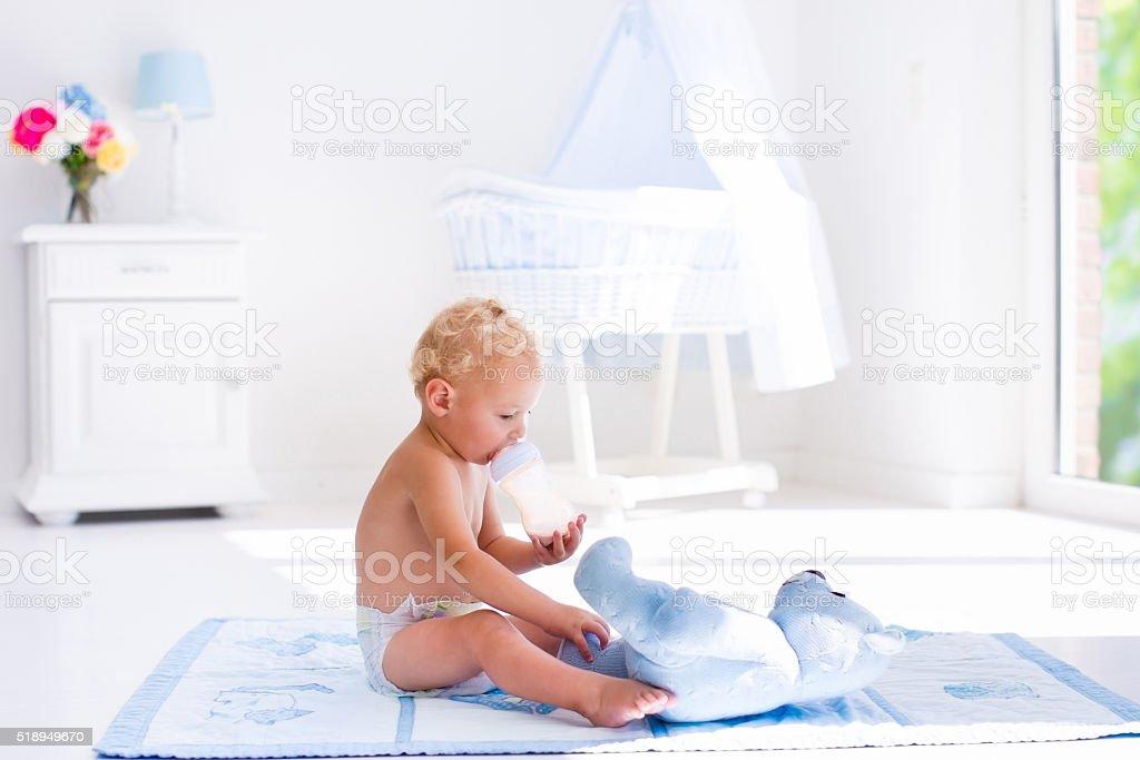Little baby boy with milk bottle in sunny nursery foto