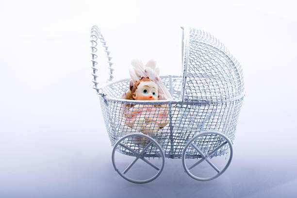 Little baby doll in baby  carriage stock photo